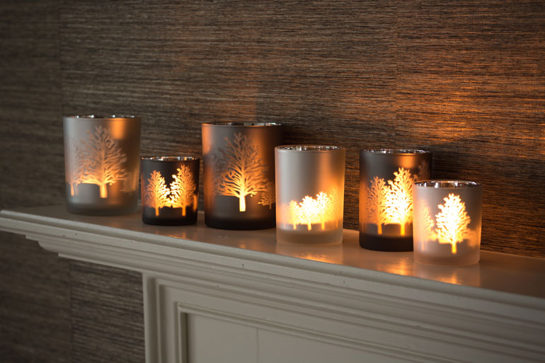 A frosted votive candle collection with Christmas patterns.