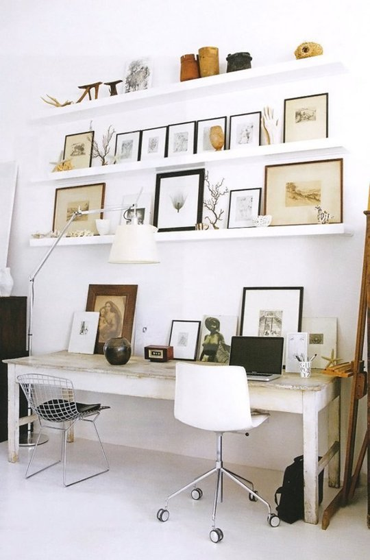 Pictures on a desk and on shelves propped against a white wall