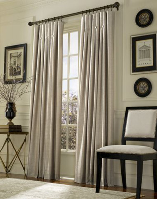 Window with cream floor length curtains