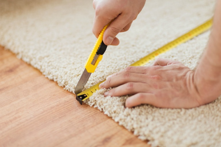 Image of somebody laying a carpet and cutting it to size