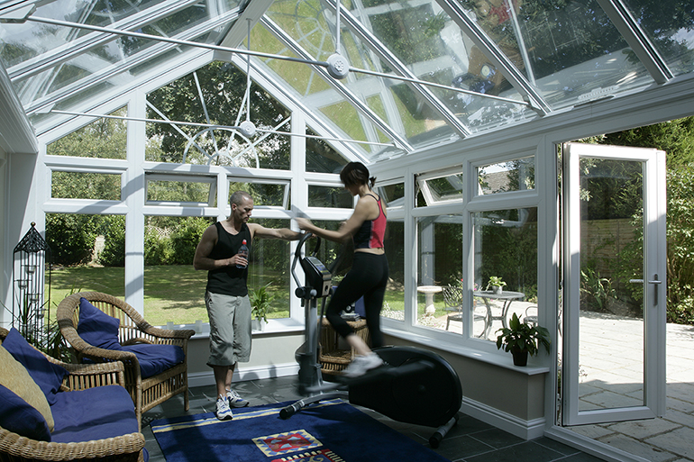 Couple on a cross trainer in their conservatory