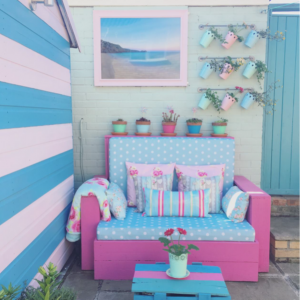 blue and pink shed and handmade outdoor bench with pastel coloured flower pots