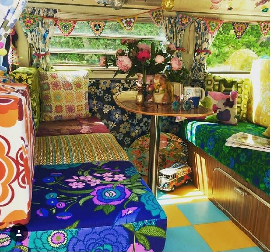 bright and colourful campervan living space with vintage style cushions and decorations