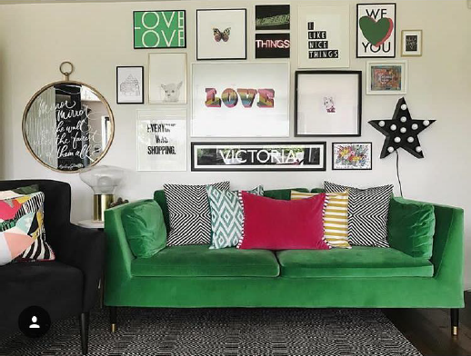 green sofa with black and white art and photos on wall behind