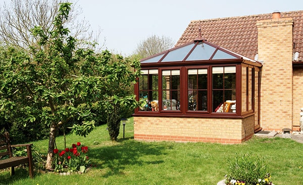 Large dark woodgrain uPVC conservatory with decorative finial from Anglian Home Improvements