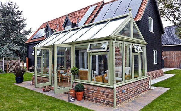 Large uPVC garden room conservatory finished in Sage Green from the Anglian conservatory range