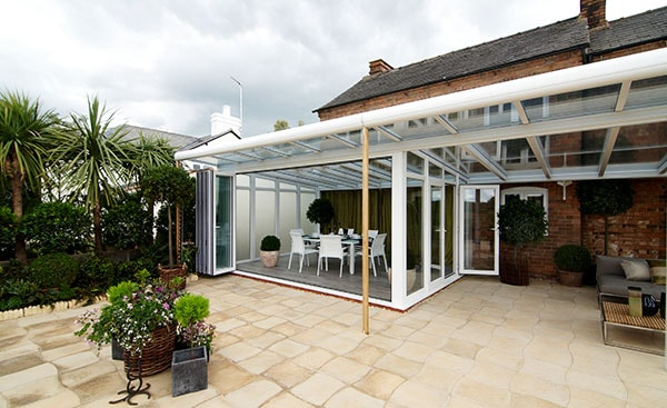 Large white uPVC veranda conservatory with aluminium bifold doors from Anglian Home Improvements