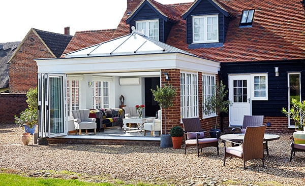 Large white orangery with bifold doors and timber casement windows from the Anglian orangery range