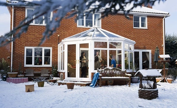 Large white uPVC Elizabethan conservatory with French doors in the snow