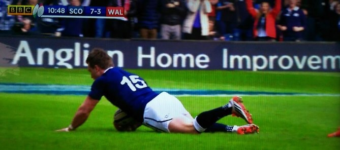 Scotland scoring a try in front of Anglian's billboard