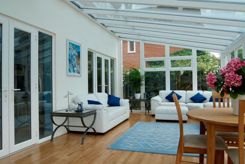 Conservatory with white sofas and timber flooring