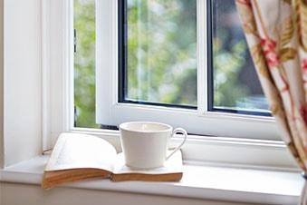 cup and book on window sill