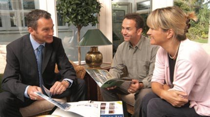 Anglian salesman shows product options to couple during an Anglian home visit